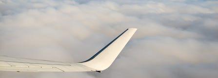Asa de um avião nas nuvens Fotos de Stock Royalty Free
