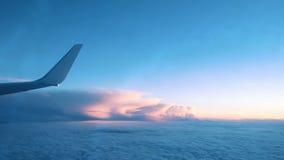 Asa de um avião de uma janela que voa sobre as nuvens de um plano no por do sol vídeos de arquivo
