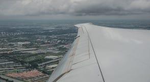 Asa de um avião de voo com fundo da arquitetura da cidade fotografia de stock royalty free