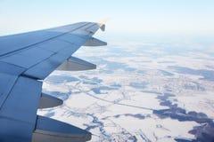 Asa dos aviões e vista superior da cidade pequena neve-coberta Imagens de Stock