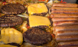 Asado a la parilla de las hamburguesas de los perritos calientes Imagen de archivo