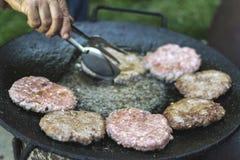 Asado a la parilla de las hamburguesas en el aceite caliente Fotos de archivo