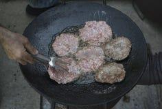 Asado a la parilla de las hamburguesas en el aceite caliente Imagenes de archivo