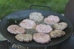 Asado a la parilla de las hamburguesas en el aceite caliente Fotografía de archivo libre de regalías
