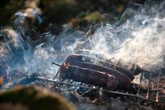 Asado a la parilla de las salchichas en acampar Imágenes de archivo libres de regalías