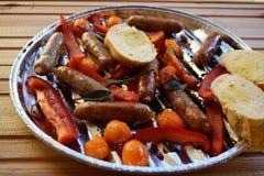Asado a la parilla de las salchichas y verduras y especias en la parrilla Fotografía de archivo