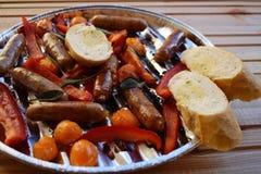 Asado a la parilla de las salchichas y verduras y especias en la parrilla Fotografía de archivo libre de regalías
