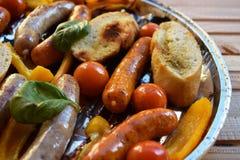 Asado a la parilla de las salchichas y verduras y especias en la parrilla Foto de archivo