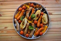 Asado a la parilla de las salchichas y verduras y especias en la parrilla Fotos de archivo libres de regalías