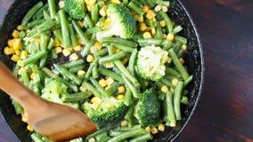 Asado a la parilla del bróculi en una cacerola del arrabio con las habas y el maíz Cámara lenta almacen de metraje de vídeo