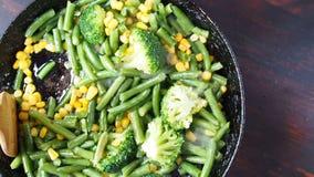 Asado a la parilla del bróculi en una cacerola del arrabio con las habas y el maíz Cámara lenta metrajes