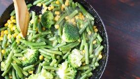Asado a la parilla del bróculi en una cacerola del arrabio con las habas y el maíz Cámara lenta almacen de video