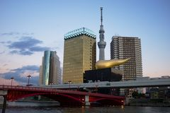Asahi beer headquarter. TOKYO, JAPAN - December 2014: Skytree Tower, Asahi Breweries Headquarter and Asahi Beer Hall with its distinctive gold Flamme d'Or icon Stock Image