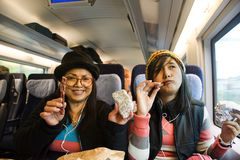 Asain妇女照顾和吃快餐的女儿并且听在手机的音乐在火车 免版税库存照片