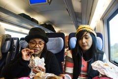 Asain妇女照顾和吃快餐的女儿并且听在手机的音乐在火车 库存照片