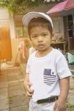 Asain泰国男孩看起来严重的穿戴一个白色盖帽 库存图片