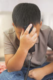 Asain boy heads down on the phone Royalty Free Stock Photography