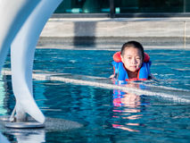 Asain boy in a swimming pool wearing a life vest Stock Photo