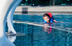 Asain boy in a swimming pool wearing a life vest Royalty Free Stock Images