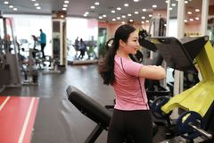 Asain chinese smiling people exercising in the gym. Sports, power. Fitness, sport, training, gym and lifestyle concept -  smiling woman exercising in the gym Royalty Free Stock Photo