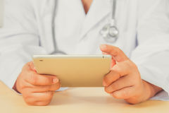 Asain female doctor diagnoses by using tablet. Royalty Free Stock Images