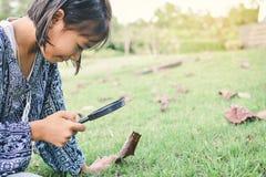 Asain girl hand holding magnifying glass in garden Stock Photos