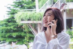 Asain girl`s smiling and using smart phone , happy time and taking mobile telephone royalty free stock image