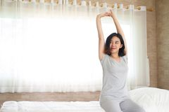 Asain girl stretching in bed Stock Photos