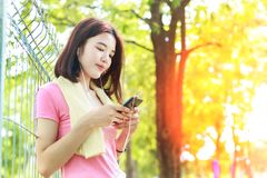 Asain girl texting while taking a break before exercise in city. Park.Attractive fit young woman in a gym with smart phone Royalty Free Stock Image