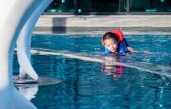 Asain-Junge in einem Swimmingpool, der eine Schwimmweste trägt lizenzfreie stockbilder
