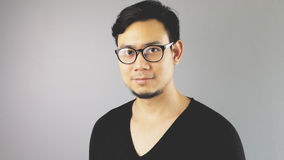 Asain man with grey background. A close-up of asian eyeglasses man with black t-shirt royalty free stock photos