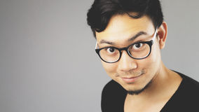 Asain man with grey background. A close-up of asian eyeglasses man with black t-shirt is looking at the camera royalty free stock photography