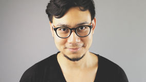Asain man with grey background. A close-up of asian eyeglasses man with black t-shirt is looking at the camera royalty free stock image