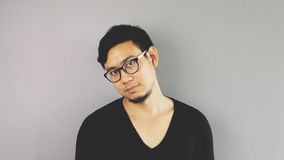 Asain man with grey background. A close-up of asian eyeglasses man with black t-shirt is looking at the camera stock photos