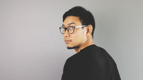 Asain man with grey background. A close-up of asian eyeglasses man with black t-shirt is looking at the camera royalty free stock photo