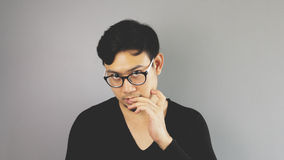 Asain man with grey background. A close-up of asian eyeglasses man with black t-shirt is looking at the camera and biting his nails royalty free stock image
