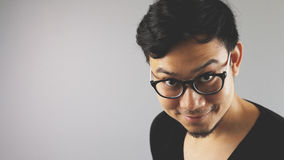 Asain man with grey background. A close-up of asian eyeglasses man with black t-shirt is looking at the camera with evil face stock photography