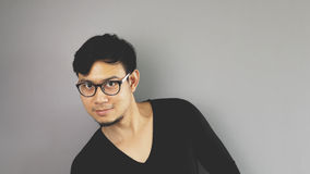 Asain man with grey background. A close-up of asian eyeglasses man with black t-shirt is looking at the camera with funny pose royalty free stock image