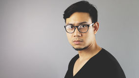 Asain man with grey background. A close-up of asian eyeglasses man with black t-shirt is looking at the camera seriously stock images