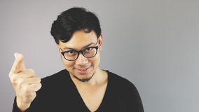 Asain man with grey background. A close-up of asian eyeglasses man with black t-shirt is looking at the camera and showing correct hand sign stock photo