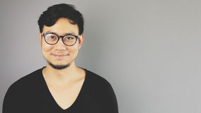 Asain man with grey background. A close-up of asian eyeglasses man with black t-shirt is looking at the camera with a small nice smile royalty free stock photography