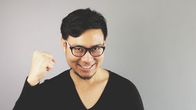 Asain man with grey background. A close-up of asian eyeglasses man with black t-shirt is looking at the camera wiht his fist on as he won stock photos