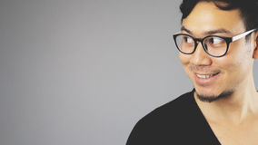 Asain man with grey background. A close-up of asian eyeglasses man with black t-shirt is looking at an empty content on the left stock images