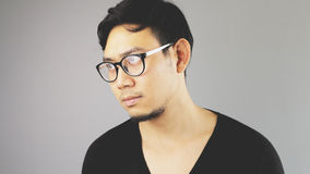 Asain man with grey background. A close-up of asian eyeglasses man with black t-shirt is looking out stock image