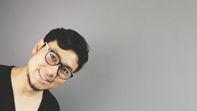 Asain man with grey background. A close-up of asian eyeglasses man with black t-shirt pops up from the corner stock photos