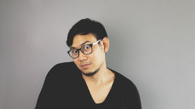 Asain man with grey background. A close-up of asian eyeglasses man with black t-shirt is raise his shoulder as he does not care royalty free stock image