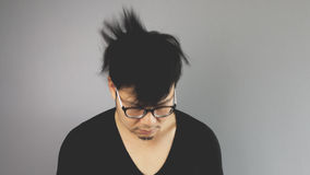 Asain man with grey background. A close-up of asian eyeglasses man with black t-shirt is shaking his head up and down royalty free stock image