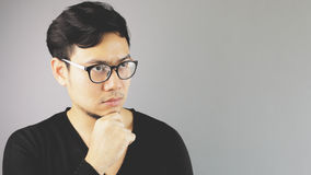 Asain man with grey background. A close-up of asian eyeglasses man with black t-shirt is thinking royalty free stock image