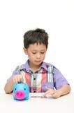 Asain pojke som räknar mynt från piggybank Royaltyfria Foton