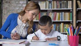 Asain potomstw macierzysty pomaga syn z nauką, kobiety mówi żartować, siedzący za stołem, azjatykci dzieciak robi pracie domowej, zdjęcie wideo